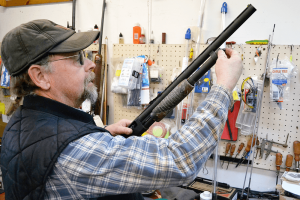 Bill Fairbrother works on a shotgun at his gun shop, Buck-N-Bears, in Mexico. Gunsmithing work makes up a small but significant part of the business, which Fairbrother runs with his wife and sons.