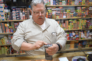 Skip Steinbrecher, owner of SharpShooters Gun Store in Richland, opens a box of ammunition. Small gun shops often stock hard-to-find firearms and ammunition that big box stores do not.