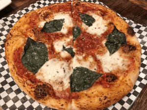 The margherita pizza presents fresh mozzarella, basil, and tomato sauce.