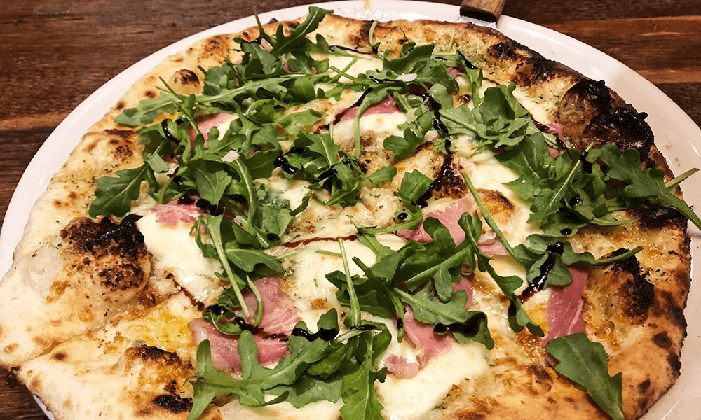 The prosciutto and arugula pizza balances Italian meat and flavorful greens, topped with a balsamic glaze.