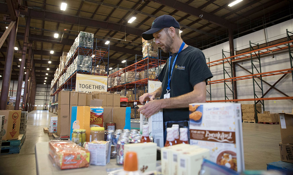 A worker sorts types of food in the Food Bank of Central New York's warehouse in Syracuse. Photo provided.