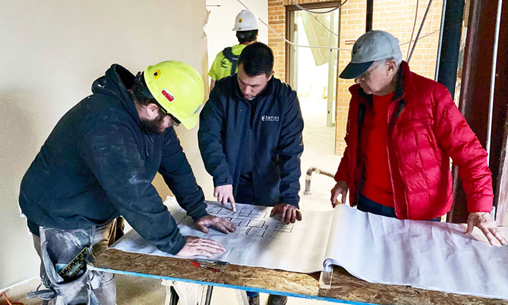 Empire Contractors Owner/President Gary McGuire (center) reviews Aqua Spa construction blueprints with employee Alex Earle (left) and Aqua Spa Project Manager Bob LeRoy.