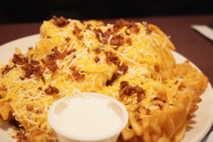 The loaded waffle fries with cheddar cheese and bacon bits ($8.99).