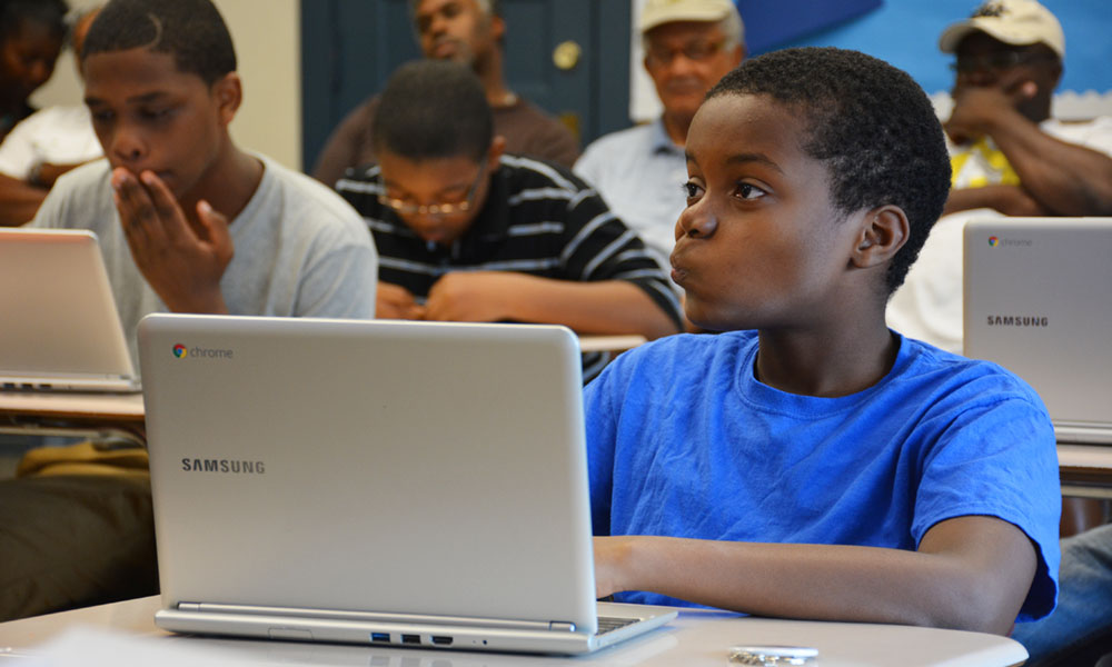 Students take part in a program sponsored by 100 Black Men of Syracuse. The nonprofit organization offers STEM activities, SAT exam preparation classes, wellness walks, reading groups and outings — all to encourage students to consider higher education, such as college tours.