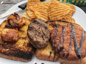 The Trifecta: One bacon-wrapped scallop, one crab cake, and one 3 oz. filet medallion all served open-faced on Texas toast, plus a side of homemade chips.