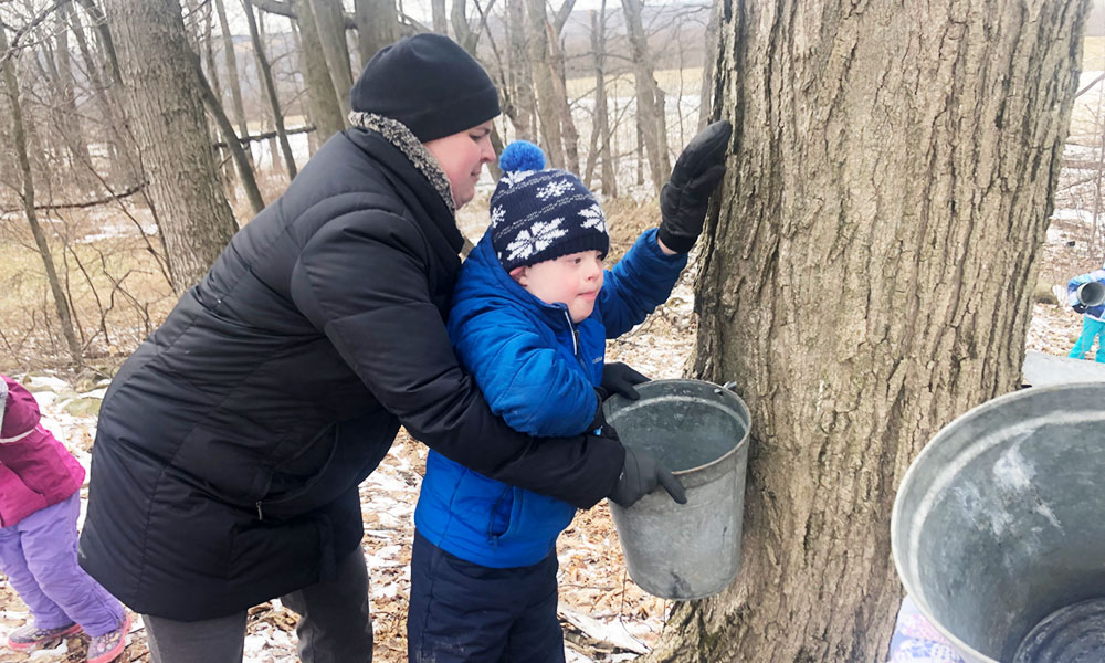 Jennifer Powers helps her son, David, work sap off a maple tree in their property.