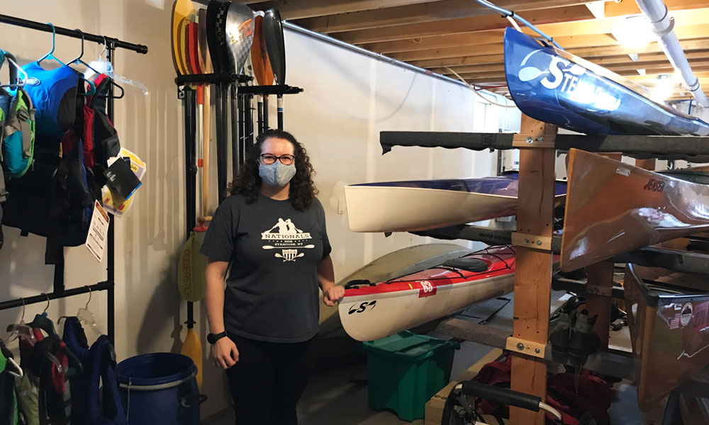 Emily Hart shows off some of the kayaks, canoes and gear in the basement of the home owned by her and husband Chris Legard, which serves as home base for their new business, Tug Hill Outfitters.