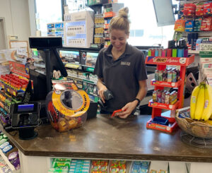 """Morgan Delles, the store manager at Delles Corner Store in Syracuse, has received no responses to an employment ad posted for two months. """"I think people don't want to work when you could sit at home and get extra money from unemployment,"""" she says."""