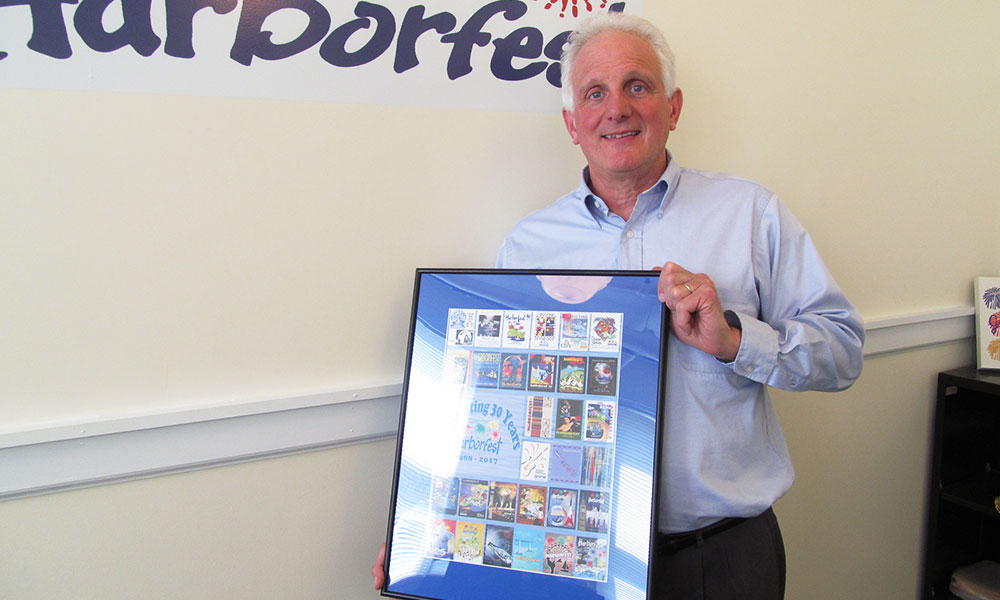 Peter Myles holds a poster commemorating 30 years of Harborfest, in 2017.