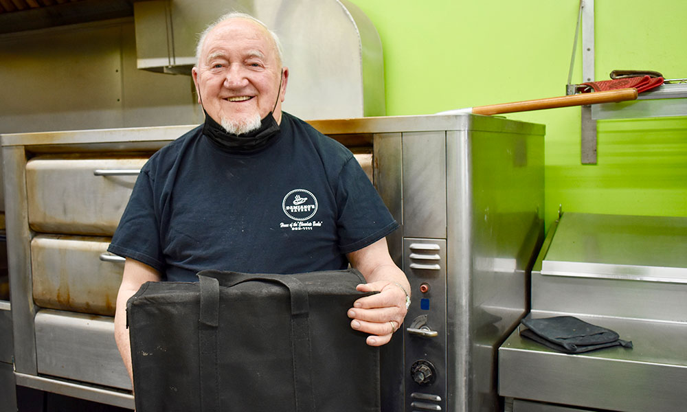 Norman Dann of Palermo is ready for his shift at Damiano's Eatery in Mexico. The 80-year-old stepped back into the workforce after his stepdaughter had problems finding drivers to deliver pizza.