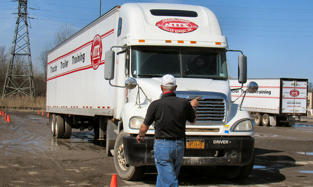 An instructor working with a student driver at National Tractor Trailer School (NTTS) in Liverpool. Since 1971, the school has trained and placed thousands of people into professional driving careers.