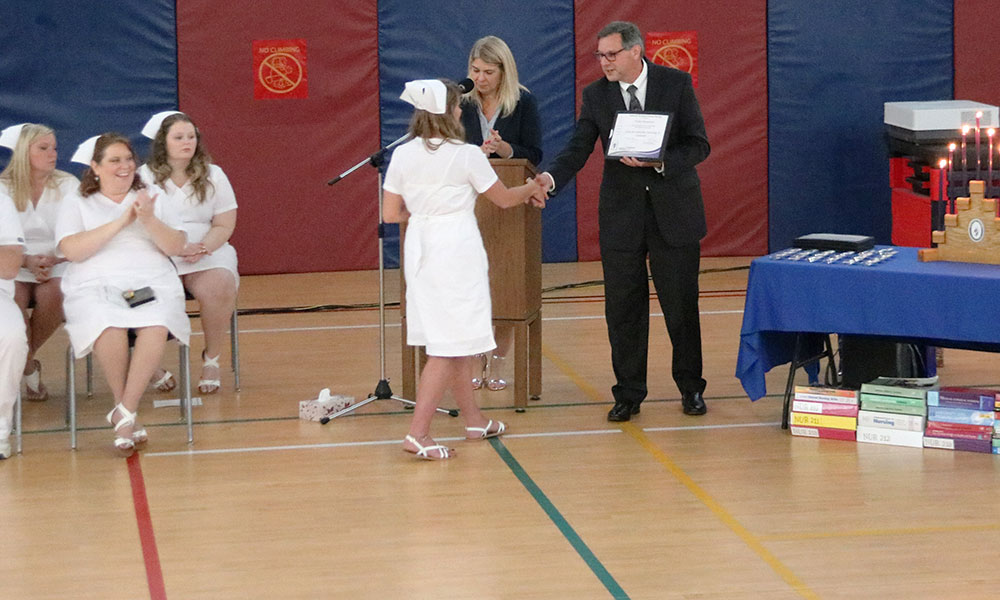 Mark LaFountain, assistant superintendent for personnel at the CiTi BOCES in Mexico, shaking hands with a student at a recent LPN graduation ceremony. Photo provided.