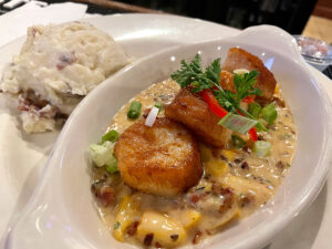 Seared scallops sat atop a medium-thick creamy sauce featuring pieces of bacon and fresh peaches.